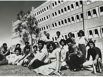 Old black and white photo of medical students sitting on the lawn in front of the Basic Sciences Building