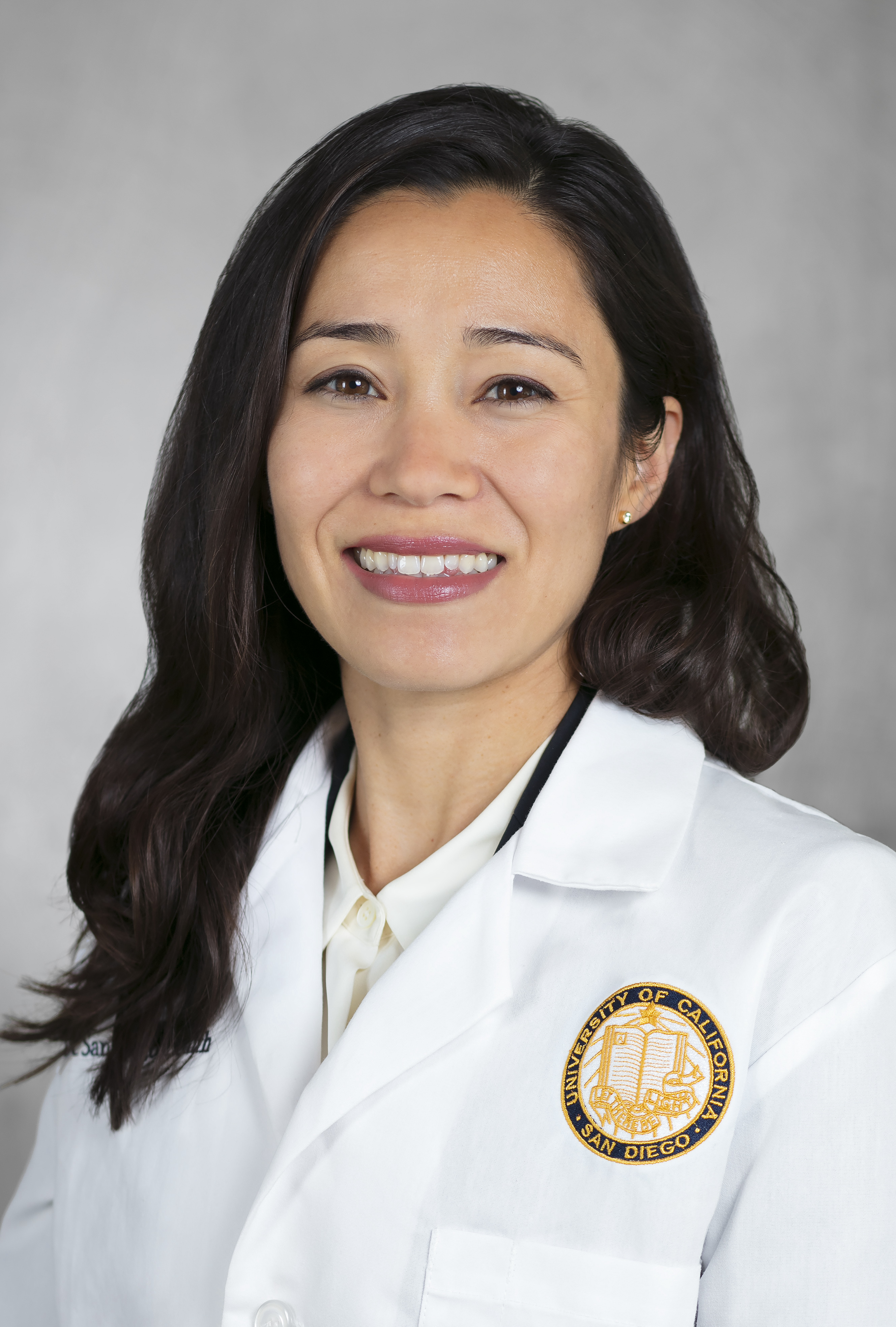 headshot of a woman with long dark hair wearing a white lab coat