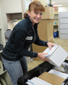 CTRI clinical coordinator Lorraine Daly packing a crate at the East Campus Office Building