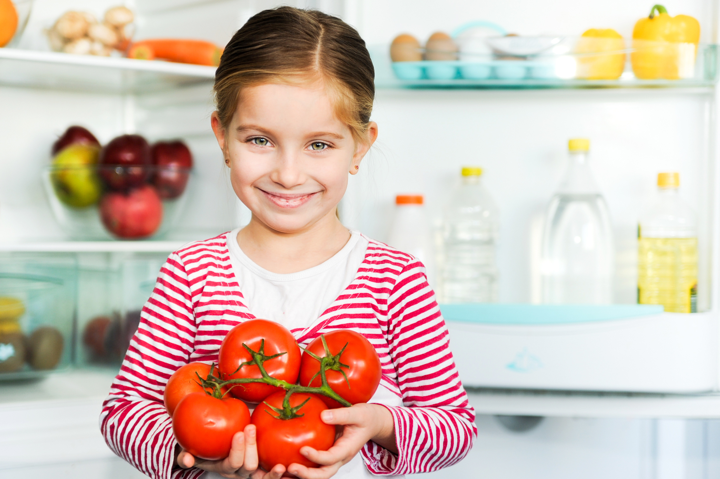 child holding tomatoes
